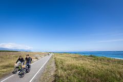 TAIWAN, HUALIEN - JANUARY 2014: A pair of unidentified tourists riding bicycle and explores the natural scenery along Taiwan`s royalty free stock image