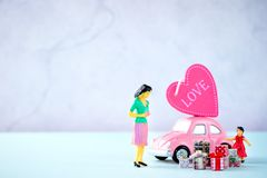 Taiwan, Tainan - April 17, 2018: Miniature people: A mother who is given a heart in love and gifts by little child girl with littl. E bettle pink car, the Stock Photos