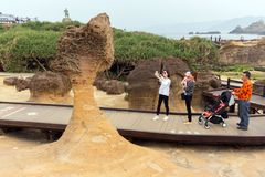 Taiwan Yehliu geologic rock formation. YEHLIU, TAIWAN - MARCH 30, 2017 : Some tourists are photographing an amazing geologic natural sandstone formation at the Royalty Free Stock Photo