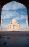 Taj Mahal DoorWay Silhouette Nobody Blue Sky Cloud. White marble of Taj Mahal framed through the silhouette of east jawab large door with nobody present on a Stock Photo