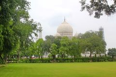 Taj Mahal view from green trees, Agra, India. Taj Mahal is an ivory-white marble mausoleum on the south bank of the Yamuna river in the Indian city of Agra. It Stock Images