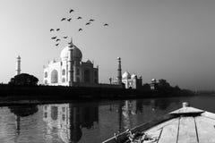 Taj Mahal in Yamuna-Riviermening wordt weerspiegeld van houten boot die in zwart-wit royalty-vrije stock afbeelding