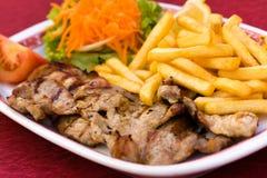 Tajada de cerdo con las patatas fritas y la ensalada de la zanahoria Fotografía de archivo