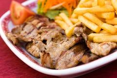 Tajada de cerdo con las patatas fritas y la ensalada de la zanahoria Imagen de archivo libre de regalías
