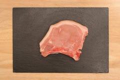 Tajada de cerdo en pizarra Imagenes de archivo