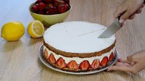 Taje una rebanada de torta de la fresa con un cuchillo