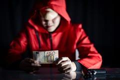 Tajemnica mężczyzna w czerwonym hoodie mienia euro banknocie obrazy royalty free