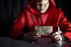 Tajemnica mężczyzna w czerwonym hoodie mienia euro banknocie fotografia stock