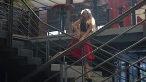 Tajemnicza dziewczyna w świetle słonecznym pozuje w spódnicie po środku schodków w centrum handlowym czerwonym czerń wierzchołku  zdjęcie wideo