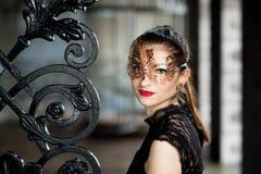 Tajemnicza kobieta w venetian karnawał masce blisko dokonanego żelaza bramy Zdjęcia Stock