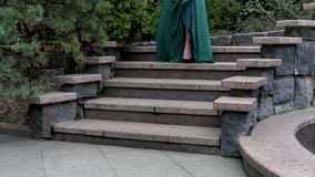 Tajemnicza kobieta w zielonej wieczór sukni, szpilkach i Pochodzi kroki w ogródzie Kobieta iść na dacie zdjęcie wideo