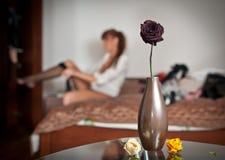 Tajemnicza rudzielec stawia jej pończochę z kwiatami i wazowym przedpolem Zmysłowej kobiety opatrunkowy up obsiadanie na łóżku i  Fotografia Stock