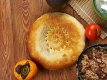 Tajik non flatbread. Tajik cuisine, non- flatbread found throughout Central Asia. , Traditional assorted Tajik dishes, Top view royalty free stock photography