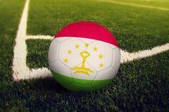 Tajikistan ball on corner kick position, soccer field background. National football theme on green grass.  stock illustration