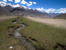 tajikistan Corriente de la montaña que fluye abajo de los picos estériles o Fotos de archivo