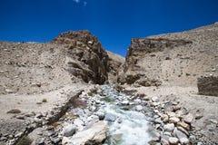 tajikistan Corriente de la montaña que fluye abajo del barranco con la barra Fotografía de archivo
