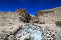 tajikistan Corriente de la montaña que fluye abajo del barranco con la barra Foto de archivo libre de regalías