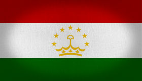 Tajikistan flag. Composed by three horizontal lines, red top one, a center white line and a dark green at the bottom, golden crown with seven stars, fabric Royalty Free Stock Image