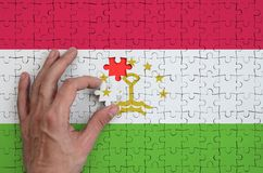 Tajikistan flag is depicted on a puzzle, which the man`s hand completes to fold.  royalty free illustration