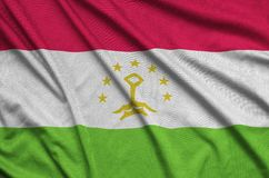 Tajikistan flag is depicted on a sports cloth fabric with many folds. Sport team banner stock images