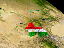 Tajikistan with flag on Earth Stock Images