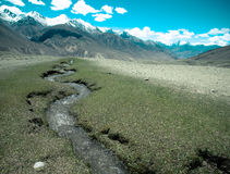 Tajikistan. Mountain stream flowing down from the barren peaks o. F the Pamirs. Tinted Stock Image