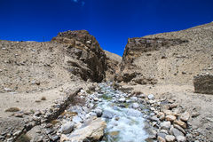 Tajikistan. Mountain stream flowing down the canyon with the bar Royalty Free Stock Photo