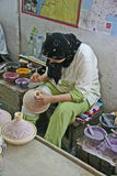 Tajine-decorating. In one of the many potteries in Fes, this woman is decorating tajines royalty free stock photo