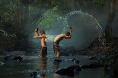 Tajlandia chłopiec bawić się wodnego pluśnięcie na zatoczce z przyjaciółmi obraz stock