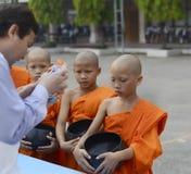 TAJLANDIA, CHIANG MAI-MARCH 25,2013: Młodzi nowicjuszów michaelita zbierają fotografia royalty free