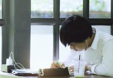Tajlandia Hatyai na 04/05/2019 Tajlandia studen jest pisać i uczący się w papierowych chees w kawiarnia sklepie obraz stock