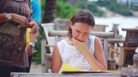 Tajlandia, Koh Samui, 19 2015 Grudzień Młoda kobieta wybiera jej rozkaz z menu i odpoczywa w plaża barze 1920x1080 zbiory