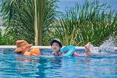 TAJLANDIA PHUKET, 20 MARCOWYCH 2018-Mom z małą córką wokoło w nadmuchiwanych armbands i pływaniem w plenerowym basenie, tło palma obraz stock
