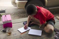 Tajlandzcy dzieci i writing praca domowa na notatniku studiują przy drewnianym t Zdjęcie Royalty Free