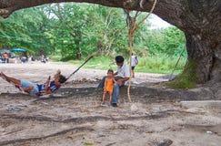 Tajlandzcy ludzie ma odpoczynek pod cieniem stary drzewo blisko Kat plaży na Phuket, Tajlandia Fotografia Stock