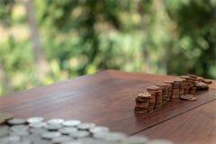 Tajlandzcy skąpanie monety 25 satang udziały na drewnianym stole z zamazanym tłem, pieniądze Tajlandia, inwestycji i oszczędzania zdjęcia royalty free