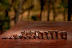 Tajlandzcy skąpanie monety 25 satang udziały na drewnianym stole z zamazanym tłem, pieniądze Tajlandia, inwestycji i oszczędzania obrazy royalty free