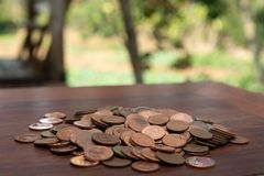 Tajlandzcy skąpanie monety 25 satang udziały na drewnianym stole z zamazanym tłem, pieniądze Tajlandia, inwestycji i oszczędzania obraz royalty free