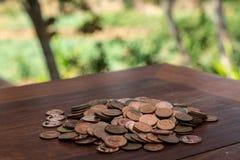 Tajlandzcy skąpanie monety 25 satang udziały na drewnianym stole z zamazanym tłem, pieniądze Tajlandia, inwestycji i oszczędzania zdjęcie royalty free