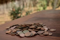 Tajlandzcy skąpanie monety 25 satang udziały na drewnianym stole z zamazanym tłem, pieniądze Tajlandia, inwestycji i oszczędzania fotografia royalty free