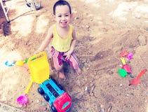 Tajlandzka chłopiec palying na stosie piasek z zabawką i plastikowym rozwidleniem Obraz Stock