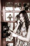 Tajlandzka dziewczyna opowiada z moda telefonem w czerni i whit Fotografia Royalty Free