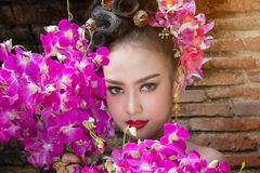 Tajlandzka kobieta jest ubranym trpical tajlandzką suknię z kwiatu tłem, po obraz royalty free