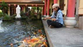 Tajlandzka kobiety podróży wizyta i żywieniowy jedzenie galanteryjny karp w stawie chińczyk uprawiamy ogródek w Udon Thani, Tajla zbiory wideo