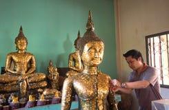 Tajlandzka mężczyzna próba łatać złotą folię przy statuą Buddha w świątyni Zdjęcia Stock
