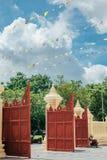 Tajlandzki czerwony świątynny drzwi z zielonym drzewem i niebieskim niebem z chmurą Obrazy Royalty Free