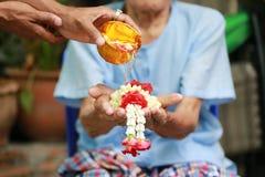 Tajlandzki festiwal Songkran, młody człowiek nalewa czystą wodę i kwiaty na rękach starszy mężczyzna, Wodna błogosławieństwo cere obrazy stock
