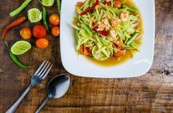 Tajlandzki jedzenie, melonow?w pomidory, sa?atka, pieprze i condiments na drewnianym stole, zdjęcia royalty free