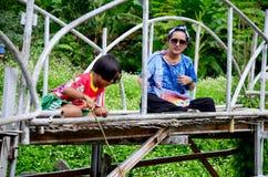 Tajlandzki kobieta portret z dziećmi łowi na bambusa moscie przy półdupkami Obrazy Stock