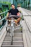 Tajlandzki mężczyzna siedzi przy Jeździeckim trójkołowem na moscie nad Pai Rive Mae Hong syn Tajlandia Fotografia Stock